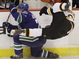 Vancouver Canucks left wing Mason Raymond sends Boston Bruins left wing Brad Marchand flying with a hip check.