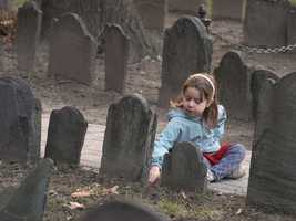 Emily Johnston, 5, of Newport, R.I., examines a gravestone at the Old Granary Burial Ground.