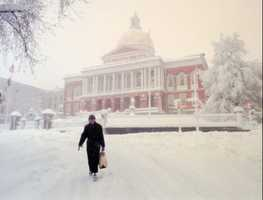 Louise McCarren of Boston passes a snow covered Massachusetts Statehouse.