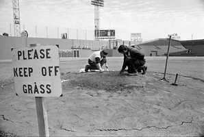 "Workmen, seen beyond a ""Please Keep Off Grass"" sign, adjust the height of the pitcher's mound in preparation for the opening game for the Boston Red Sox, April 16, at Fenway Park in Boston, March 15, 1973."