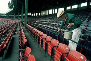Rick Duncanson works Friday applying the finishing touches of paint to the stands at Fenway Park in Boston, April 1, 1988, in preparation for Monday, the opening day of baseball when the Red Sox will meet the Detroit Tigers.
