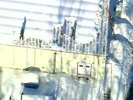 Workers clear snow on the roof of a Comcast facility in Westford, Mass.