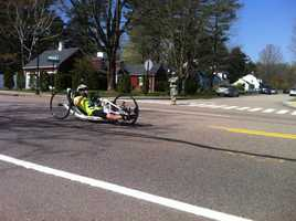 A wheelchair racer blows kisses to the crowd.
