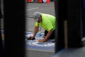 A volunteer gets the finish line ready.