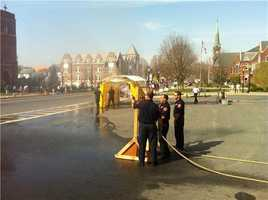 Natick Firefighters adjusting hoses that were to be used to cool down the runners, next to the misting tent.