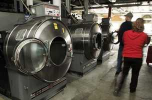 Bidders walk by industrial washers in the basement of the Balsams Hotel in Dixeville Notch.