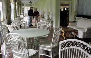 Bidders look at furniture on the Sun Deck of the Balsams Hotel