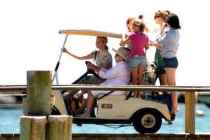 Swift on the back of a golf cart driven by Ethel Kennedy.