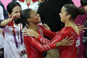 U.S. gymnast Gabrielle Douglas hugs teammate Alexandra Raisman after Raisman's floor exercise during the Artistic Gymnastic women's team final