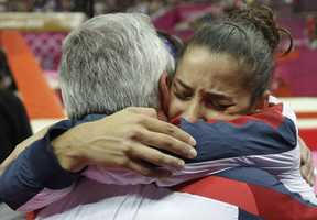 Alexandra Raisman hugs coach Mihai Brestyan after results were amended and she was declared winner of the bronze medal during the artistic gymnastics women's apparatus finals for the beam.