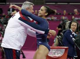 Alexandra Raisman hugs coach Mihai Brestyan after her performance on the floor during the artistic gymnastics women's apparatus finals.
