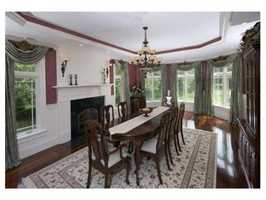 The dining room features a coffered ceiling, bay window, and hardwood flooring.