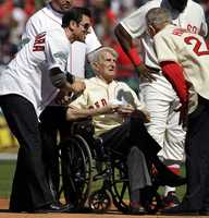 Johnny Pesky, center, is greeted by former player Nomar Garciaparra, left, and others during a celebration of the 100th anniversary of Fenway Park on April 20, 2012.