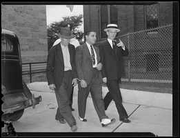 Later the head of the New England Mafia, Raymond Patriarca is seen here in this photo after his arrest for a holdup.  Patriarca was charged during his teenage years for hijacking, armed robbery, assault, safecracking, and auto theft. He was indicted as being an accessory to murder in 1934.