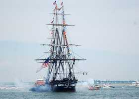 USS Constitution fires a 21-gun salute toward Fort Independence.