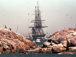 The USS Constitution is towed by a tugboat into Marblehead Harbor, July 20, 1997, on its 200th birthday trek from Boston. Thousands of people on sea and land watched the oldest commissioned warship afloating by its own power for the first time in 116 years.