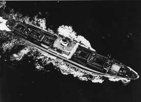 "Soviet ships carrying nuclear equipment steamed toward Kennedy's ""quarantine"" zone around the island, but turned around before reaching the line. This aerial view shows a Soviet ship carrying eight canvas-covered missiles and transporters, visible on decks."