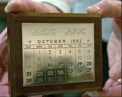 A curator of the John F. Kennedy Libary in Boston holds a commemorative calendar that President Kennedy gave to all of his staff involved with the Cuban Missile Crisis meetings in 1962. This calendar, with the days 16-28 in bold type, was the copy given to then first lady Jacqueline Bouvier Kennedy by the president.