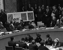 In this Oct. 25, 1962 file photo, U.S. Ambassador Adlai Stevenson, far right, describes aerial photographs of launching sites for intermediate range missiles in Cuba during an emergency session of the United Nations Security Council at U.N. Headquarters at the height of the Cuban Missile Crisis.