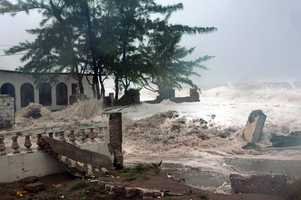 Waves, brought by Hurricane Sandy, crash on a house in the Caribbean Terrace neighborhood in eastern Kingston, Jamaica.