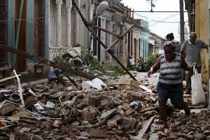 Residents walk through the rubble from homes that were damaged by Hurricane Sandy in Santiago de Cuba, Cuba, Friday Oct. 26, 2012.