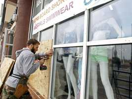 A worker boards up the windows of the store as Hurricane Sandy approaches in Ocean City, Md., on Saturday, Oct. 27, 2012.