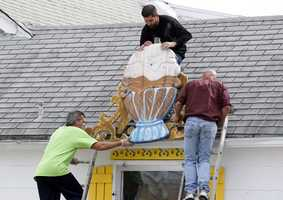 Jerry Velez, top, Richard Caguilat, left, and William Disburger, right, remove a large sign from the Sea Shell Ice Cream shop in Wildwood, N.J., Saturday, Oct. 27, 2012, in preparation for Hurricane Sandy.