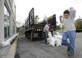 Felix Garcia, owner of Garcia 's Landscaping carries sandbags to line the edge of a commercial building located next to a canal to prepare for the arrival of Hurricane Sandy on Sunday, Oct., 28, 2012, in Amityville, N.Y.