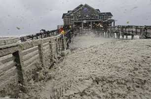High winds blow sea foam onto Jeanette's Pier in Nags Head, N.C., Sunday, Oct. 28, 2012 as wind and rain from Hurricane Sandy move into the area.
