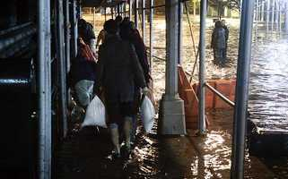 Residents carry sandbags to slow flooding to their building as the East River overflows into the Dumbo section of the Brooklyn borough of New York, as Sandy moves through the area, on Monday, Oct. 29, 2012.