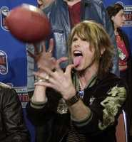 Aerosmith lead singer Steven Tyler clowns around as he flips a football after a Super Bowl XXXV Halftime Show news conference Thursday afternoon, Jan. 25, 2001, in Tampa, Fla.