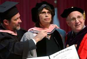 Rock and Roll legend Steven Tyler, center, receives an honorary Doctor of Music degree from Provost Harry Chalmiers, left, and college President Lee Eliot Berk, during Berklee College of Music's 2003 commencement, Saturday, May 10, 2003, in Boston.