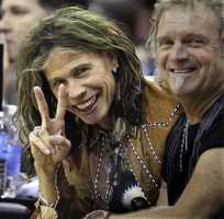 Aerosmith frontman Steven Tyler, left, gestures as he and drummer Joey Kramer watch the Boston Celtics and the Cleveland Cavaliers in an NBA basketball game Wednesday, Oct. 27, 2010, in Cleveland.
