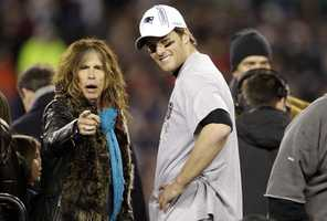 Aerosmith lead singer Steven Tyler and New England Patriots Tom Brady interact on the podium during the trophy presentation ceremony following the AFC Championship NFL football game against the Baltimore Ravens on Sunday, Jan. 22, 2012, in Foxborough, Mass. The Patriots defeated the Ravens 23-20 to win the AFC Championship.