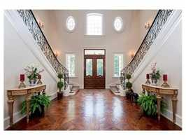 The home features a custom wrought iron double staircase.