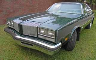 "JC's first car was a 4-door 1977 Olds Cutlass.  ""Friends would write notes on the fabric roof.  It died the day before I left for college.  I still love that car,"" she says."