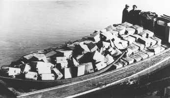 Coast guardsmen stand on a speed boat packed with nearly 700 cases of liquor they captured as it was unloaded at Newburyport, Mass., on the morning of May 6, 1932. They pursued the craft from outside the harbor into the Merrimack River. The crew fled as the government boat approached.