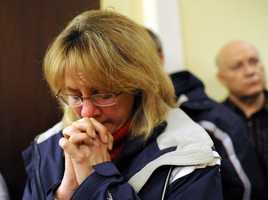 A mourner bows her head inside the St. Rose of Lima Roman Catholic Church at a vigil service for victims of the Sandy Hook Elementary School shooting.