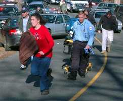 In this photo provided by the Newtown Bee, paramedics and others rush toward Sandy Hook Elementary School.