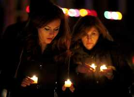 Katy Caulfield, left, and her mother, Irene Caufield, hold candles to place at a makeshift memorial near the elementary school where a day earlier a gunman opened fire.