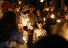 Mourners gather for a candlelight vigil at Ram's Pasture to remember shooting victims in Newtown, Conn.