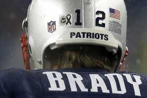 A small black ribbon to honor the victims of the Sandy Hook Elementary School shootings in Newtown, Conn., is affixed to the helmet of New England Patriots quarterback Tom Brady as he takes the field.