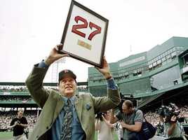 Carlton Fisk displays his framed Red Sox number 27 to fans at Boston's Fenway Park as he greets fans after his number was retired Sept. 4, 2000.