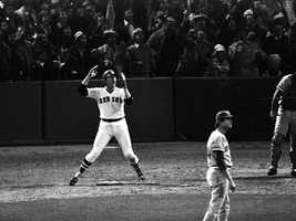 In this Oct. 22, 1975 photo, Boston Red Sox's Carlton Fisk, left, watches his 12th-inning home run against the Cincinnati Reds to win the sixth game of the World Series at Fenway Park in Boston.
