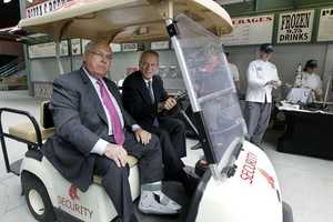 Boston Red Sox President and CEO Larry Lucchino, right, drives Boston Mayor Thomas Menino in a cart for a tour at Fenway Park in Boston on April 9, 2012.