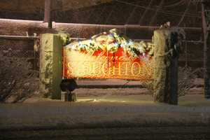 A snowcovered sign welcomes visitors to Stoughton Saturday night. Rain quickly changed to heavy, wet snow.