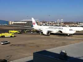 Ground photo shows the Massport fire truck around the Japan Airlines plane.