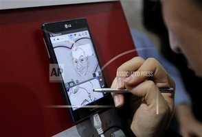 An artist draws a caricature to demonstrate the Panorama Note feature on LG smartphones.