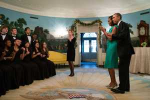President Barack Obama and First Lady Michelle Obama listen to the Seneca Valley High School Chamber Choir in the Diplomatic Reception Room of the White House following a holiday reception, Dec. 5, 2012.
