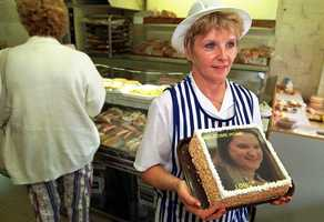 Carol Cooke holds a welcome home cake baked in the local bakery in the village of Elton for British former au pair Louise Woodward on the day that she returned home.
